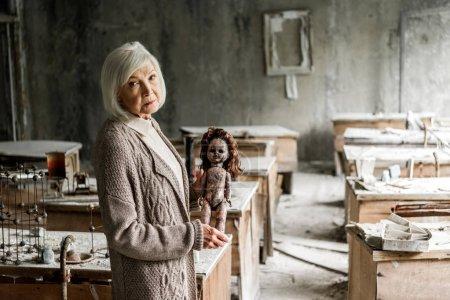 Photo pour Foyer sélectif de la femme retraitée avec des cheveux gris tenant poupée sale - image libre de droit