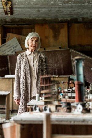 Foto de Enfoque selectivo de la mujer jubilada de pie en el aula abandonada sucia - Imagen libre de derechos