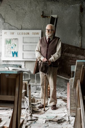 Photo pour Foyer sélectif du chapeau de fixation d'homme aîné tout en restant près du conseil avec des lettres - image libre de droit