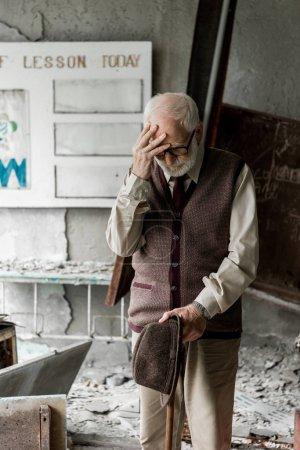 Photo pour Triste homme âgé tenant chapeau tout en se tenant près de bord avec des lettres - image libre de droit