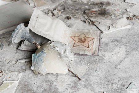 PRIPYAT, UKRAINE - AUGUST 15, 2019: broken globe near soviet union sign on dirty floor
