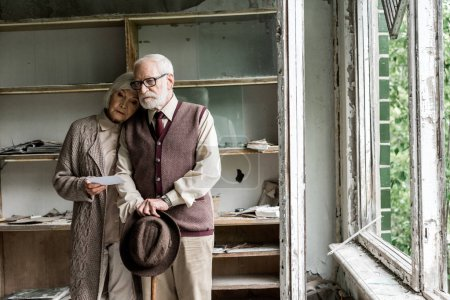 Photo for Retired woman and bearded husband standing in damaged classroom - Royalty Free Image