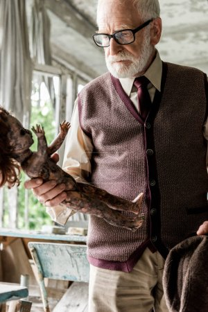 Photo pour Homme âgé barbu tenant chapeau tout en regardant la poupée de bébé brûlé dans la salle de classe - image libre de droit