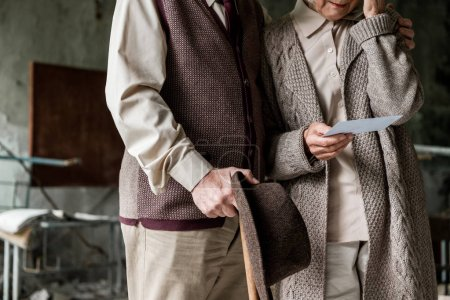 Photo for Cropped view of retired couple standing in abandoned school and holding photo - Royalty Free Image
