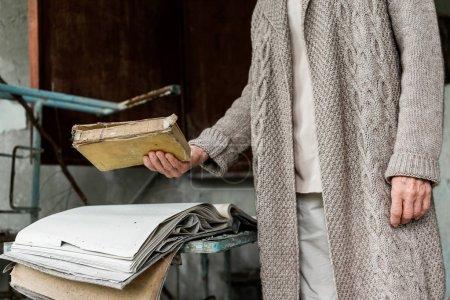 Foto de Pripyat, Ucrania - 15 de agosto de 2019: vista recortada de la mujer mayor sosteniendo libro en la mano - Imagen libre de derechos