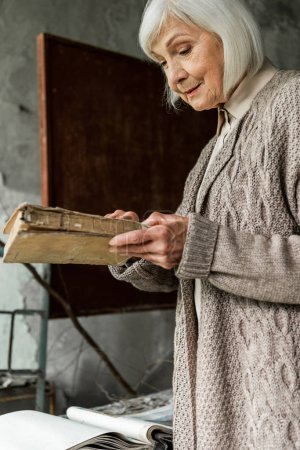 Photo for PRIPYAT, UKRAINE - AUGUST 15, 2019: retired woman with grey hair holding book in hands - Royalty Free Image