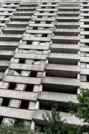 Photo pour Vue à angle bas du bâtiment avec des fenêtres près des arbres à Tchernobyl - image libre de droit