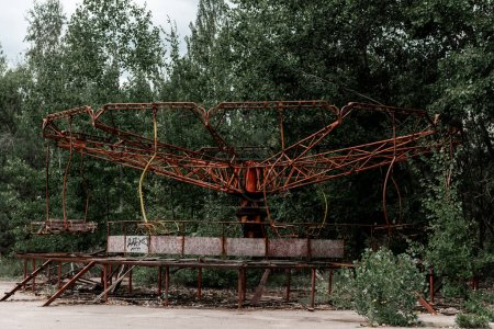 Photo for PRIPYAT, UKRAINE - AUGUST 15, 2019: abandoned red metallic carousel in green amusement park in chernobyl - Royalty Free Image
