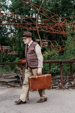 PRIPYAT, UKRAINE - AUGUST 15, 2019: bearded retired man in hat and glasses walking with walking cane and suitcase near damaged carousel