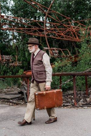 Photo pour Pripyat, Ukraine - 15 août 2019: un retraité barbu en chapeau et lunettes marchant avec une canne à pied et une valise près du carrousel endommagé - image libre de droit