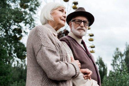 Photo pour Pripyat, Ukraine - 15 août 2019: vue à faible angle d'un homme âgé barbu debout avec sa femme à la retraite près de la grande roue dans un parc d'attractions - image libre de droit