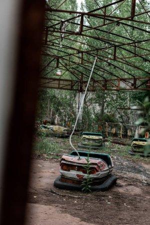 PRIPYAT, UKRAINE - AUGUST 15, 2019: selective focus of dirty bumper cars in amusement park