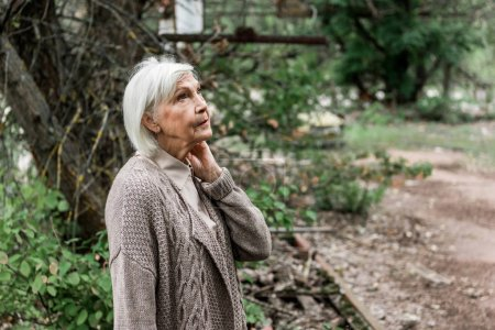Photo for Senior woman standing in green abandoned park - Royalty Free Image