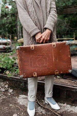 Photo pour Pripyat, Ukraine - 15 août 2019: vue recadrée d'une femme âgée tenant une valise dans un parc d'attractions - image libre de droit