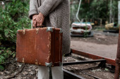 PRIPYAT, UKRAINE - AUGUST 15, 2019: cropped view of retired woman holding suitcase in amusement park