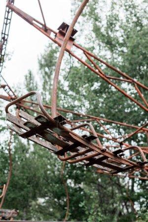 Photo pour Pripyat, Ukraine - 15 août 2019: focus sélectif du carrousel métallique rouge dans un parc d'attractions vert à Tchernobyl - image libre de droit