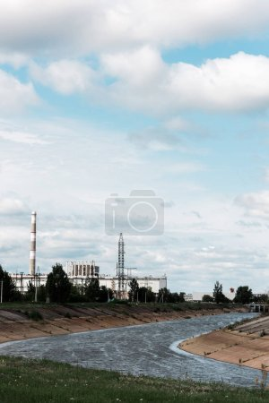 Photo for PRIPYAT, UKRAINE - AUGUST 15, 2019: abandoned chernobyl nuclear power plant near trees and river - Royalty Free Image