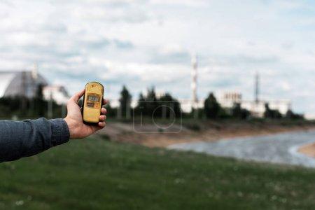 Photo pour Pripyat, Ukraine - 15 août 2019: vue recadrée de l'homme tenant un radiomètre près de la centrale nucléaire de Tchernobyl - image libre de droit