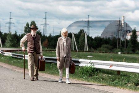 Photo pour Pripyat, Ukraine - 15 août 2019: homme et femme âgés marchant avec des bagages près du réacteur de Tchernobyl - image libre de droit