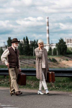 Foto de Pripyat, Ucrania - 15 de agosto de 2019: hombre y mujer de alto rango caminando con equipaje cerca de la central nuclear de Chernóbil - Imagen libre de derechos