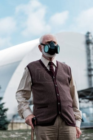 Photo for PRIPYAT, UKRAINE - AUGUST 15, 2019: senior man in protective mask standing near abandoned chernobyl reactor - Royalty Free Image