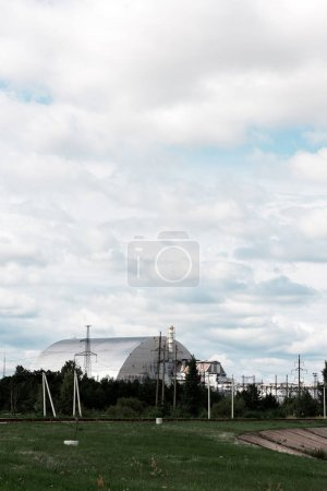 PRIPYAT, UKRAINE - AUGUST 15, 2019: abandoned chernobyl reactor near green trees against sky with clouds