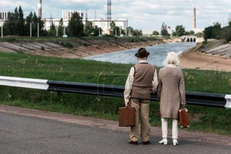 Foto de Pripyat, Ucrania - 15 de agosto de 2019: vista trasera de la pareja de la tercera edad con equipaje cerca de la central nuclear de Chernóbil - Imagen libre de derechos