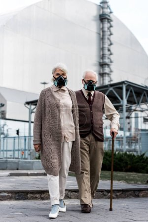 Photo for PRIPYAT, UKRAINE - AUGUST 15, 2019: senior couple in protective masks standing near abandoned chernobyl reactor - Royalty Free Image