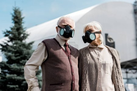 Photo for PRIPYAT, UKRAINE - AUGUST 15, 2019: retired couple in protective masks standing near abandoned chernobyl reactor - Royalty Free Image