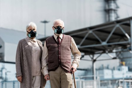 Photo for PRIPYAT, UKRAINE - AUGUST 15, 2019: senior woman and man in protective masks standing near abandoned chernobyl reactor - Royalty Free Image
