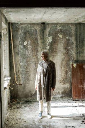 Photo pour Femme aînée avec le cheveu gris restant dans la pièce vide et sale - image libre de droit