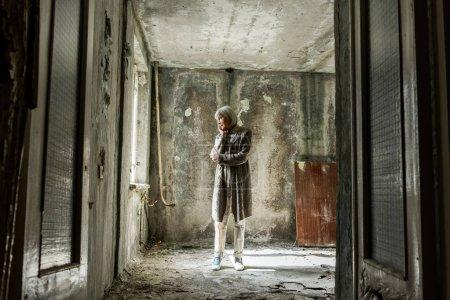 Photo pour Femme âgée bouleversée debout dans la chambre vide et sale - image libre de droit