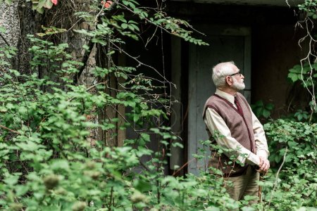 selective focus of retired man in glasses standing with walking stick near house