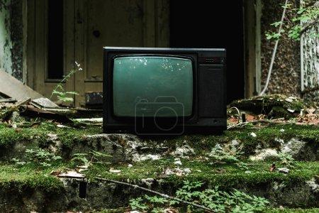 Foto de Televisión retro en escaleras verdes con moho cerca del edificio - Imagen libre de derechos