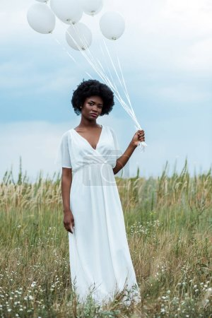 attractive african american girl in dress holding balloons in field