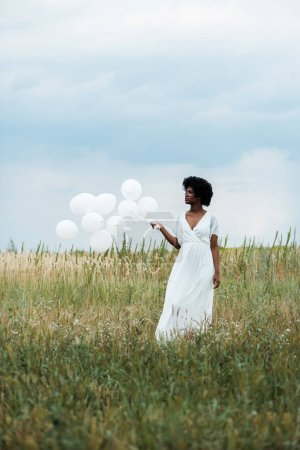Photo for Selective focus of african american girl in white dress holding balloons in field - Royalty Free Image