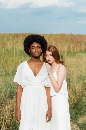 sad redhead woman standing with african american girl in field