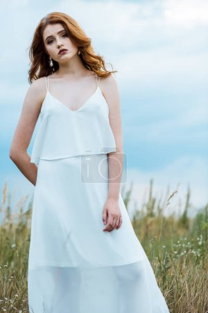 Photo for Sad and pretty young woman in dress standing in field - Royalty Free Image