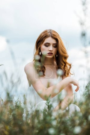 Photo for Selective focus of upset young woman sitting in field - Royalty Free Image
