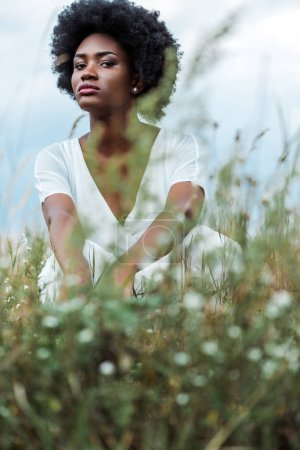selective focus of pretty african american woman in green field
