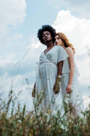 Photo pour Foyer sélectif de rousse fille debout avec afro-américaine femme contre le ciel - image libre de droit