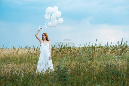 Photo for Selective focus of redhead girl holding balloons in grassy field - Royalty Free Image