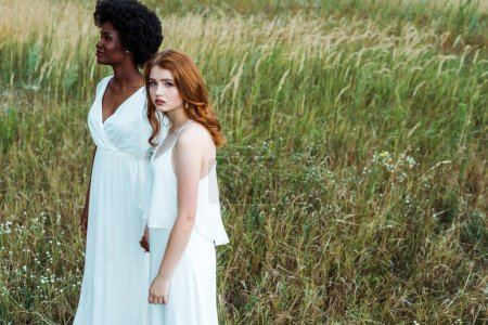 Photo for Young and pretty multicultural women standing in green field - Royalty Free Image