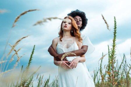 Photo pour Foyer sélectif de la femme américaine africaine étreignant la fille de rousse contre le ciel bleu - image libre de droit
