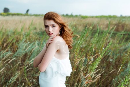 Photo for Beautiful redhead woman in white dress looking at camera - Royalty Free Image