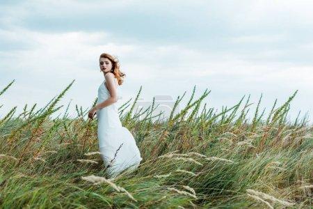Photo pour Foyer sélectif de la femme attirante de rousse dans la robe blanche regardant l'appareil-photo - image libre de droit