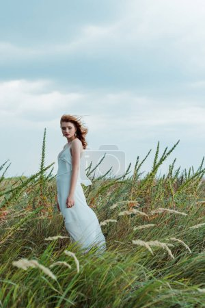 Photo for Selective focus of redhead woman in white dress looking at camera - Royalty Free Image
