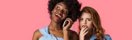 Photo for Panoramic shot of happy african american woman talking on smartphone near worried redhead girl isolated on pink - Royalty Free Image