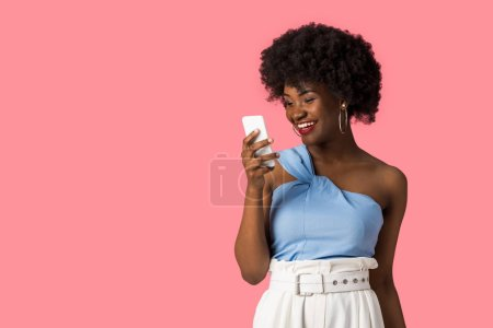 Photo for Smiling african american girl holding smartphone isolated on pink - Royalty Free Image