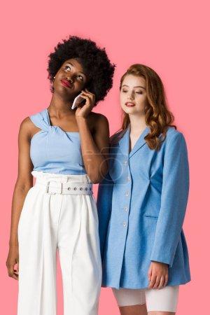Photo pour Femme américaine africaine parlant sur le smartphone près de la fille rousse d'isolement sur le rose - image libre de droit